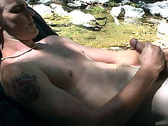 Christian sit on a lawn chair by the creek stroking himself.