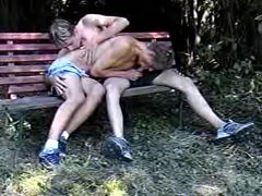 Dudes secluded on bench in park to enjoy some oral