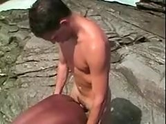 Twink does African guy on sea shore